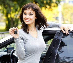 pretty girl leaning on car showing the car key