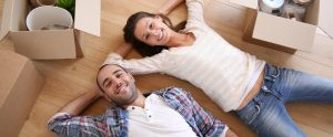 happy young couple laying together on the floor of their new house